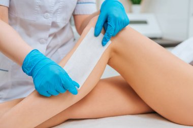 Partial view of cosmetologist in rubber gloves doing leg wax depilation