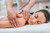 Teilansicht des Masseurs bei Rückenmassage für entspanntes Mädchen auf Massagetisch