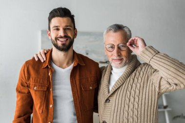 handsome man smiling while standing with cheerful senior father touching glasses