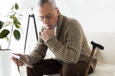pensive retired man holding photo frame while sitting on sofa near walking stick