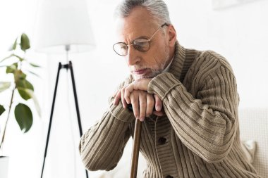 pensive retired man thinking while holding walking stick