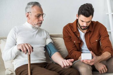 bearded man measuring blood pressure of senior father in glasses