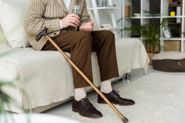 cropped view of retired man holding pill while sitting on sofa near walking cane