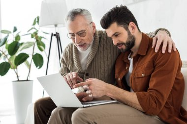 handsome bearded man pointing with finger at laptop while sitting with senior father