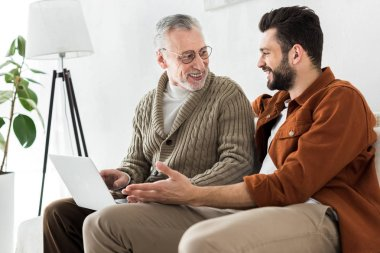 happy bearded man gesturing while sitting with senior father and looking at laptop