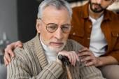 oříznutý pohled syn uvedení ruce na ramena rozrušená senior otce v brýlích