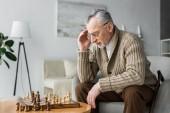töprengő nyugdíjas férfi szemüveg rövid idő játék sakk otthon gondolkodás