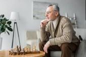 átgondolt nyugdíjas férfi gondolkodás közelében sakktábla otthon ülve szemüveg