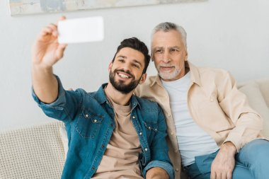 cheerful bearded man taking selfie with senior father at home