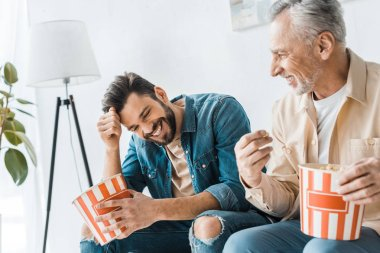 happy senior father sitting with smiling son and holding popcorn bucket