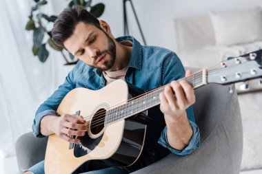 handsome bearded man playing acoustic guitar at home