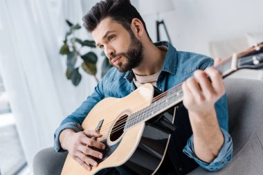bearded and handsome man playing acoustic guitar at home