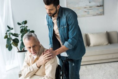 caring handsome son holding hands with disabled senior father in wheelchair at home