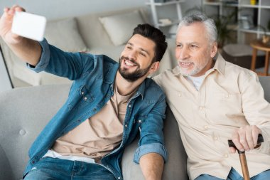 cheerful son taking selfie with retired cheerful father on smartphone