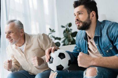 happy retired man watching championship and cheering with bearded son holding football