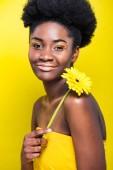 Usmívající se africká americká dívka držící květinu izolovanou na žluté