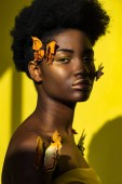 Attractive african american young woman with butterflies on yellow