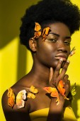 Fotografia Pensive pretty african american woman with butterflies on yellow