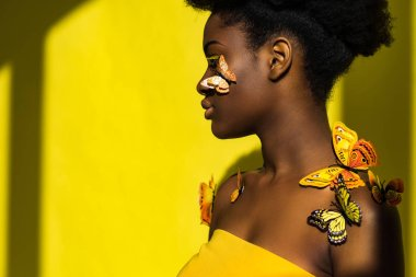 Side view of african american woman with butterflies looking away on yellow stock vector