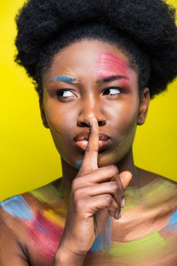 African american woman with bright makeup showing silent gesture isolated on yellow