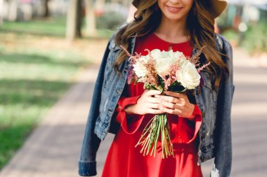 cropped view of happy woman holding flowers while standing in park