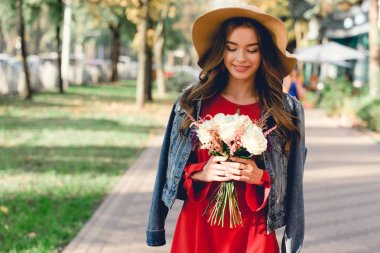 attractive girl in hat looking at flowers while standing in park
