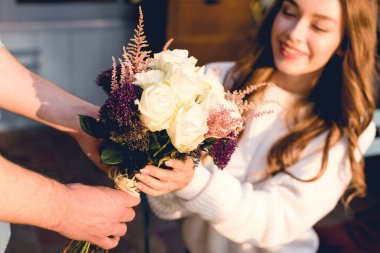 cropped view of man giving flowers to happy young woman