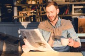 happy man reading business newspaper and holding cup of coffee