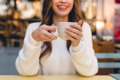 cropped view of cheerful girl holding cup with coffee in cafe