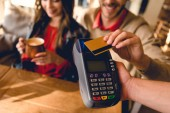 cropped view of man holding credit card while paying in cafe