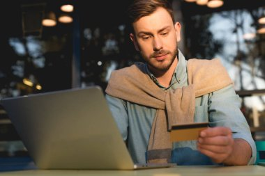 Handsome man looking at credit card while using laptop stock vector