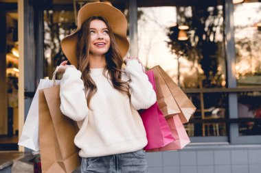 happy young woman in hat smiling while holding shopping bags