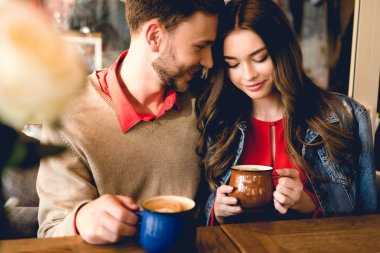 Happy bearded man looking at attractive girlfriend while holding cup of coffee stock vector