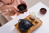 Photo cropped shot of woman holding wooden bowl with black tea in hands in morning at home
