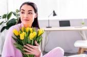 Fotografie portrét zadávací ženy s kyticí žlutých tulipánů doma