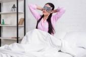 portrét ženy v růžovém pyžamku a spící maska táhnoucí se v posteli ráno