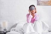nő a rózsaszín pizsama és alvó maszk ül ágyas otthon