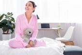 fröhliche Frau im rosa Pyjama mit Teddybär zu Hause auf dem Bett sitzend