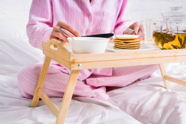 partial view of woman in pajamas having pancakes for breakfast in bed at home