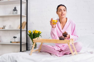 woman in pajamas with glass of orange juice and chocolate muffins on bed in morning at home