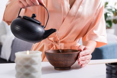cropped shot of woman making tea while having tea ceremony in morning at home