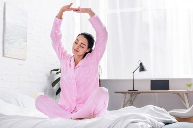 woman in pajamas stretching on bed in morning at home