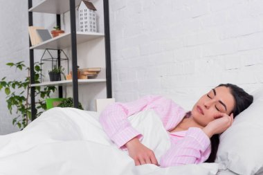 portrait of woman in pink pajamas sleeping in bed at home