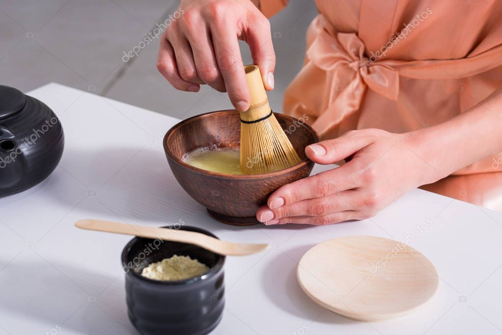 partial view of woman having tea ceremony in morning at home