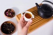 cropped shot of woman holding cup of hot tea while having tea ceremony at home