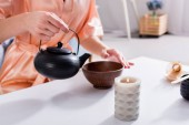 Photo cropped shot of woman making tea while having tea ceremony in morning at home