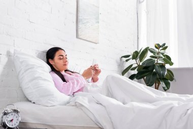 smiling woman in pajamas using smartphone while resting in bed at home