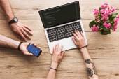 oříznuté zastřelil člověka s smartphone s logem Facebooku a drží v ruce žena u stolu s notebookem a kalanchoe květ