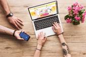 Schnappschuss eines Mannes mit Smartphone mit Facebook-Logo in der Hand und einer Frau am Tisch mit Laptop mit aliexpress-Website und Kalanchoe-Blume