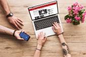 abgeschnittene Aufnahme von Mann mit Smartphone mit Facebook-Logo in der Hand und Frau am Tisch mit Laptop mit bbc-Website und Kalanchoe-Blume